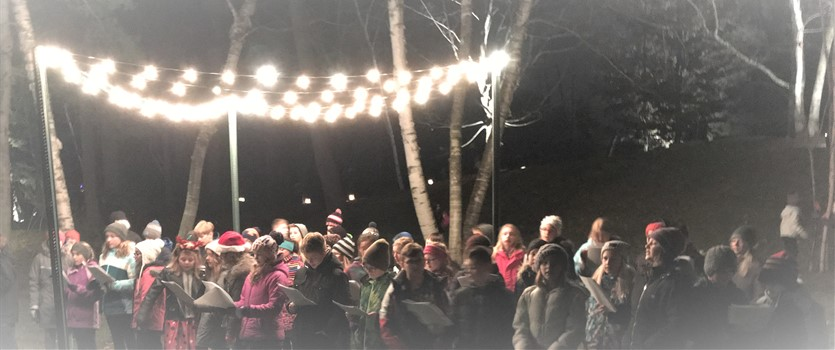 Student Choir singing outdoors under lights